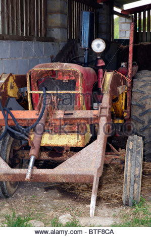an old farm tractor rusting away in a barn that is no longer in use - Stock Photo