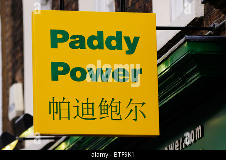 Bilingual Paddy Power Bookmaker sign, Gerrard Street, Chinatown, London, England, UK - Stock Photo