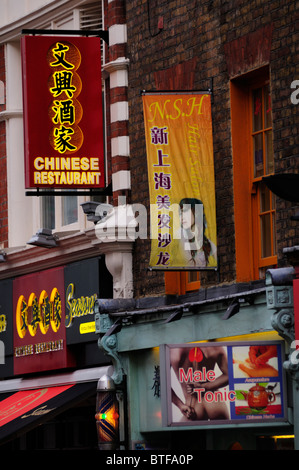 Chinese Restaurant, Hair Salon and Herbalist Shop signs on Wardour Street, Chinatown, London, England, UK - Stock Photo