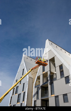 Construction workers in cherry picker bucket working on building exterior - Stock Photo