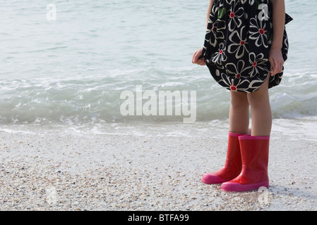 Girl standing on beach, wearing rubber boots - Stock Photo