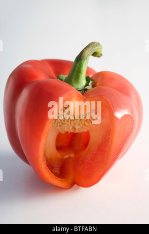 Red bell pepper with section cut out revealing tiny white seeds within - Stock Photo