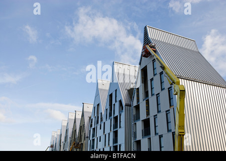 Construction workers using cherry picker crane to work on building exterior - Stock Photo