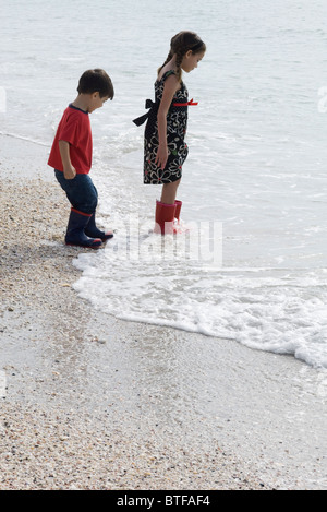 Children wading in surf at the beach - Stock Photo