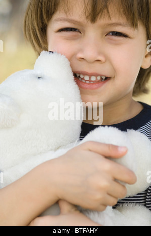 Little boy embracing teddy bear, portrait - Stock Photo