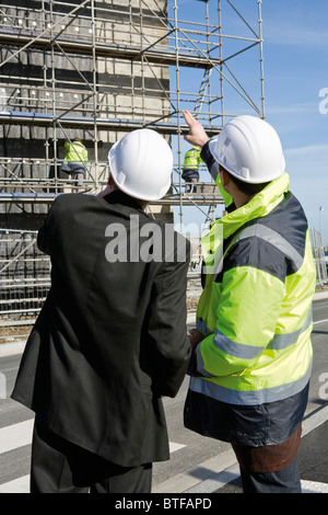 Building contractor and businessman at construction site - Stock Photo