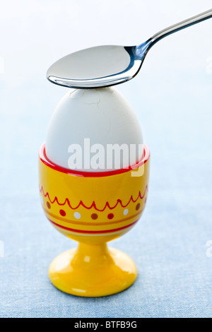 Breaking open a soft boiled egg in cup with spoon - Stock Photo
