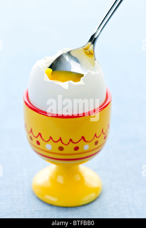 Closeup of soft boiled egg in cup with spoon - Stock Photo