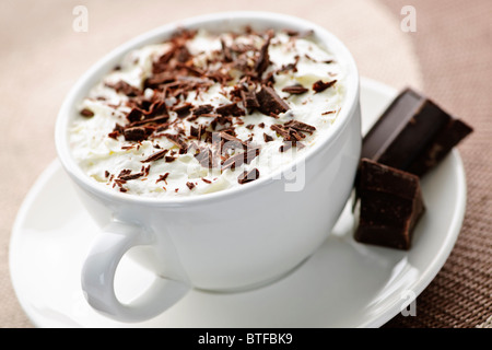 Cup of hot cocoa with shaved chocolate and whipped cream - Stock Photo