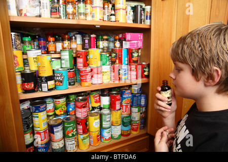boy sniffing essence from food cupboard - Stock Photo
