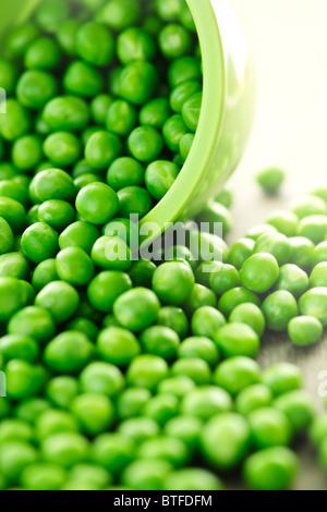 Closeup on spilling bowl of fresh green green peas - Stock Photo