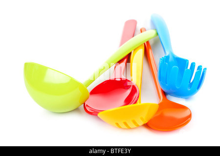 Various colorful plastic kitchen utensils on white background - Stock Photo