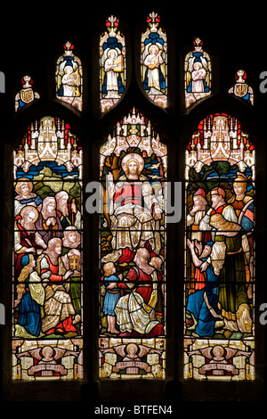 Stained glass window depicting Christ with crowd of people St Nicholas Church at Bradfield Sheffield South Yorkshire - Stock Photo