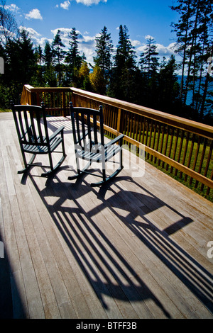 Afternoon sun throws the shadows of two rocking chairs on a deck in Bernard, Maine - Stock Photo