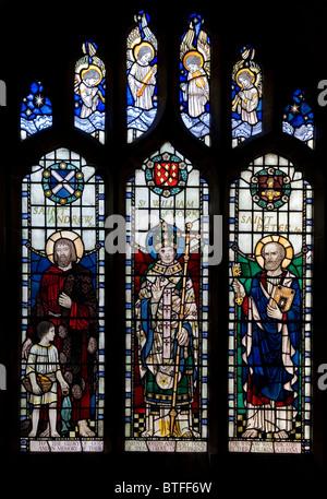 Stained glass window depicting three Saints inside St Nicholas Church at Bradfield Sheffield South Yorkshire U.K - Stock Photo