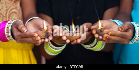 Young Indian girls holding lit oil lamps. India - Stock Photo