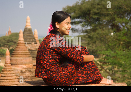Young Burmese woman in a red dress sitting on the roof of a temple , Bagan (Pagan), Myanmar (Burma) - Stock Photo