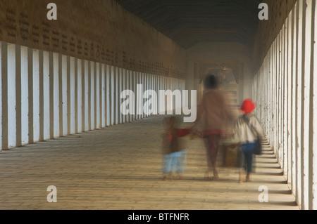 Burmese woman with her two children in the walkway to the Shwezigon Pagoda, Bagan (Pagan), Myanmar (Burma) - Stock Photo