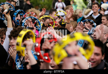 A crowd of young people holding tambourines in the air during a live music performance in Birmingham, UK - Stock Photo
