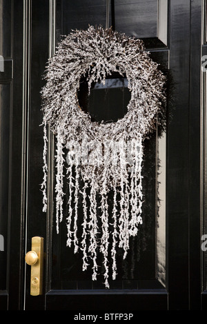 Christmas / Xmas silver wreath on a wood / wooden black Victorian / Georgian style front door. (56) - Stock Photo