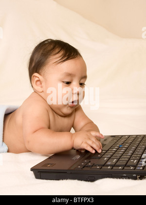Baby playing with notebook computer keyboard, typing on it - Stock Photo