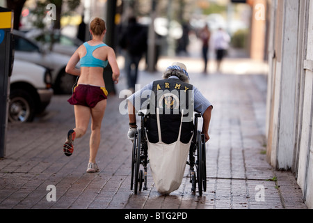 A man in a wheelchair wearing an vest emblazoned with Army insignia pushes himself up the sidewalk as woman jogs - Stock Photo