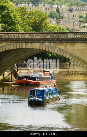 Vertical view across the river Avon in Bath with canal boats sailing along in the sunshine. - Stock Photo