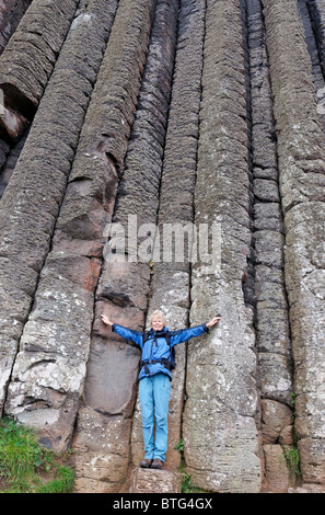 Mature woman standing at the base of the 'Organ' near to the Giant's Causeway. County Antrim, Ulster, Northern Ireland, - Stock Photo