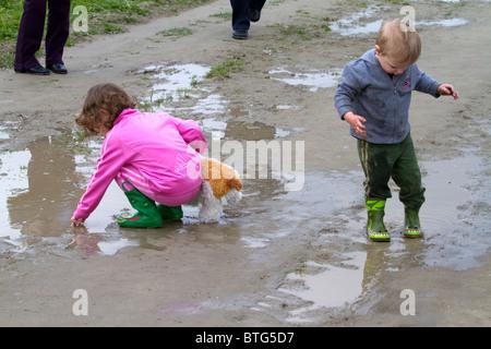 Children play in mud puddles at Skagit Valley, Washington, USA. - Stock Photo