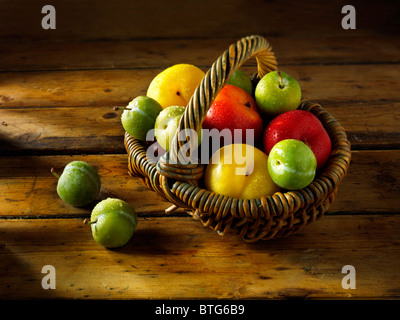 Mixed red, yellow and green plums in a basket on a wooden table - Stock Photo
