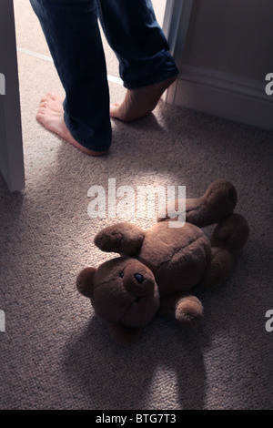 Child's teddy bear lying on the floor of a carpeted room as a man's feet step in through an open door - Stock Photo