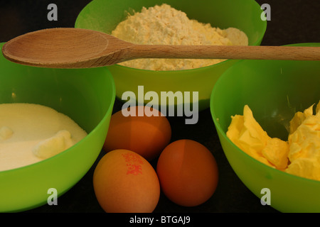 Cake ingredients; flour, sugar, butter and eggs with wooden spoon - Stock Photo