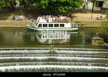Horizontal view of tourists sitting in a pleasure boat on a guided tour through Bath city centre - Stock Photo