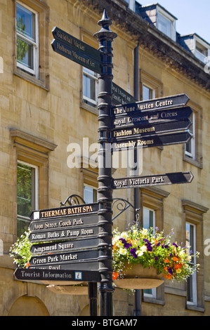 Vertical close up of an old fashioned wrought iron sign post in the centre of Bath with directions for all the tourist - Stock Photo