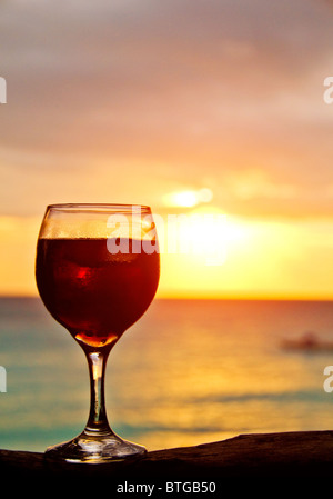 A glass of vine at the rock on romantic beach - Stock Photo
