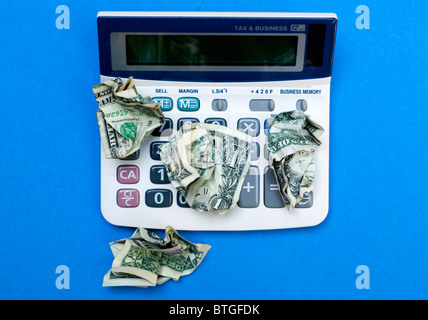 Scrunched up American dollar bills on top of calculator - Stock Photo