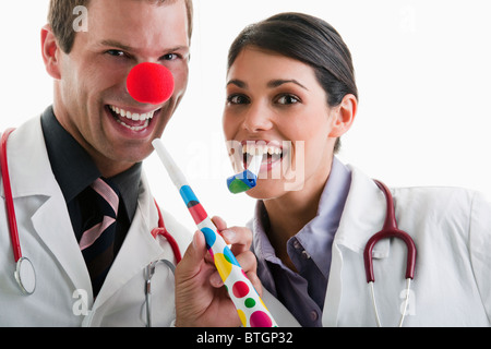Male and female doctors with party toys - Stock Photo