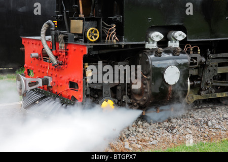 Close-up of the front of a vintage steam locomotive with steam - Stock Photo