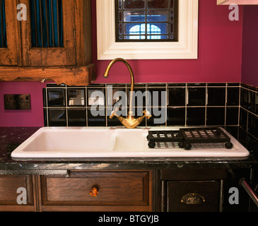 Close-up of black-tiled splash-back on wall above double white sink with brass mixer tap - Stock Photo