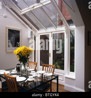 Vase Of Yellow Flowers On Glass Topped Table In Modern Conservatory Dining Room With