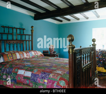 Colorful patchwork quilt on antique bed in blue country bedroom with beamed ceiling - Stock Photo