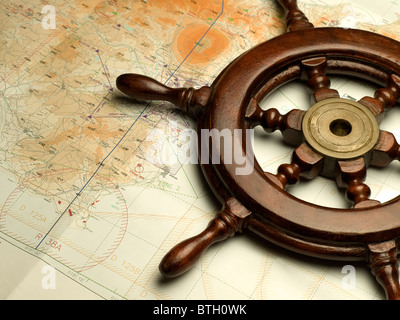 helm and nautical map, useful for various navigation or travel themes - Stock Photo