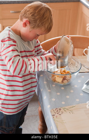 A MODEL RELEASED photo of a seven year old boy preparing cooking ingredients in the Uk - Stock Photo