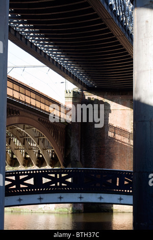 Iron footbridge and railway viaducts above Castlefield Canal Basin near Manchester England