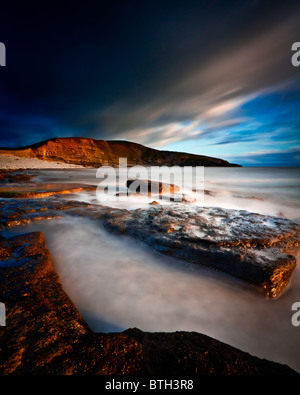 A stormy Dunraven Bay in warm evening light - Stock Photo
