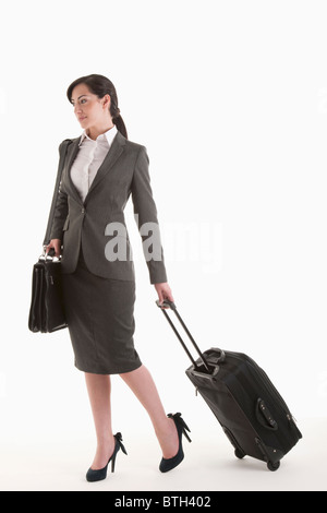 Young woman in suit with wheeled suitcase - Stock Photo