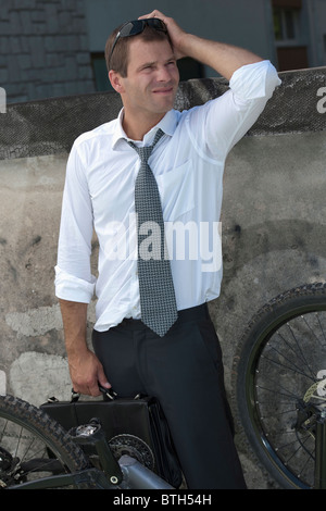 Businessman in suit next to broken bicycle - Stock Photo