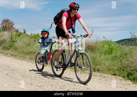 A mother and son enjoying a mountain bike ride on a forest track - Stock Photo