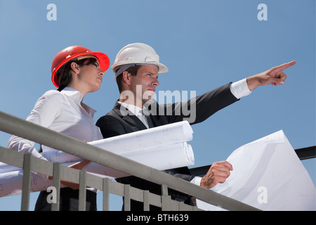 Professionals holding plans at construction site - Stock Photo