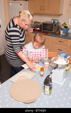 A MODEL RELEASED photo of a seven year old boy and his mum preparing cooking ingredients in the Uk - Stock Photo